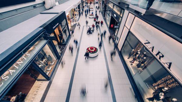 Imagem que mostra o espaço de um shopping, com várias marcas   Bárions Produções