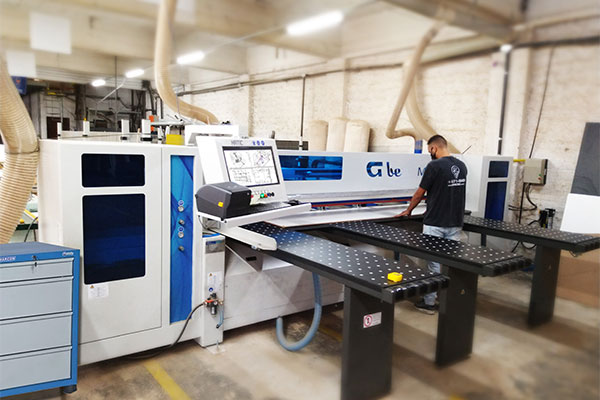 Imagem do operador trabalhando em uma máquina de corte para marcenaria moderna   Bárions Produções