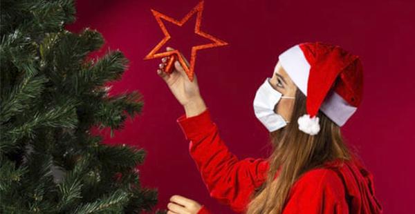 Mulher vestida de Mamãe Noel com máscara de proteção COVID-19 | Bárions